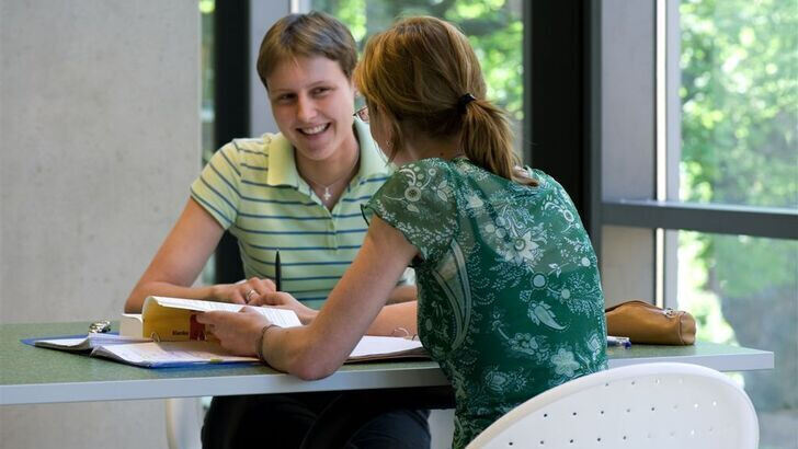 Two students speaking with each other