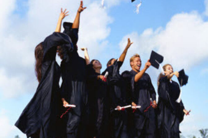 Doctoral students flinging their doctoral caps in the air